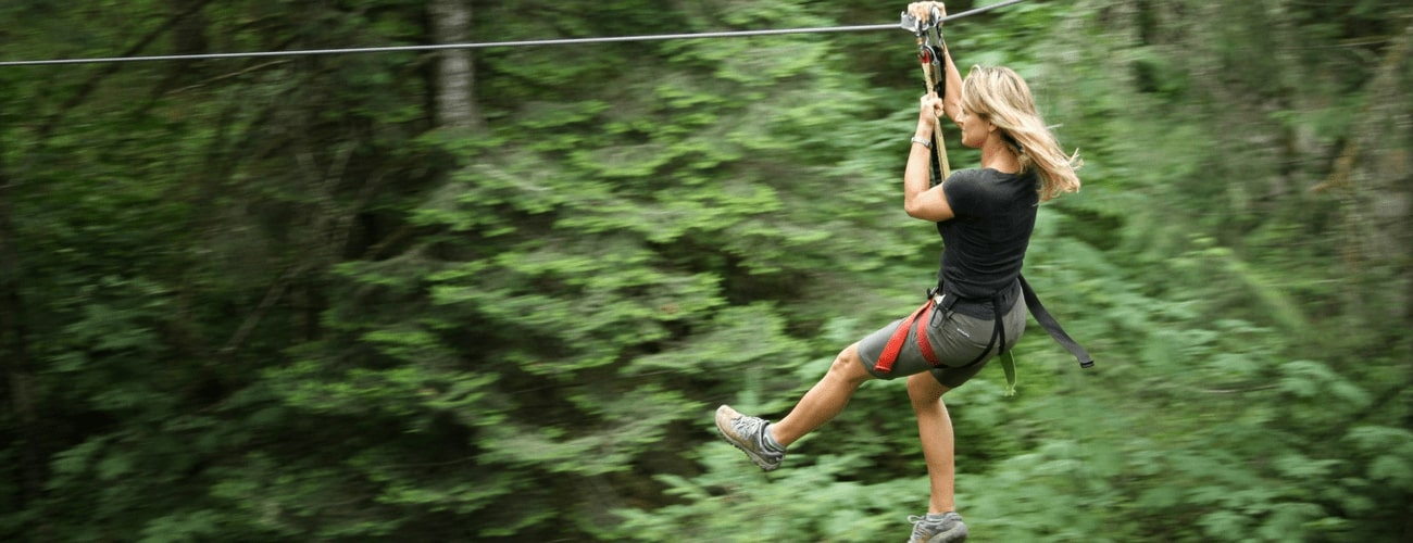 Picture of woman ziplining - Tree to Tree Adventure Park